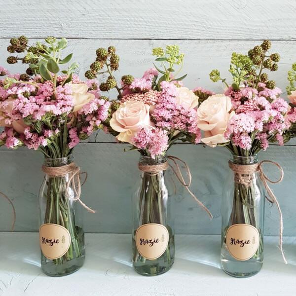 """Bouquet di statice, rosa e more confezionati in bottiglie di vetro. Idea regalo per dire """"grazie""""."""
